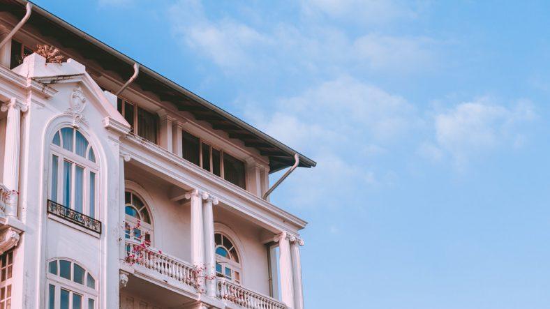 Hvid høj bygning med altan