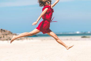 Kvinde hopper på strand fordi hun er glad