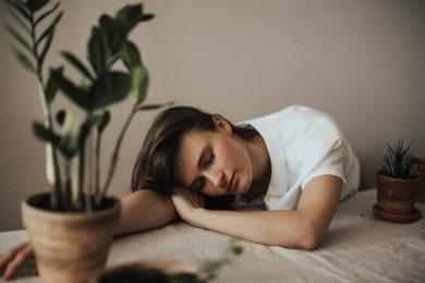 kvinde sover på bord med grøn plante på