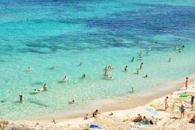strand med en masse badende mennesker