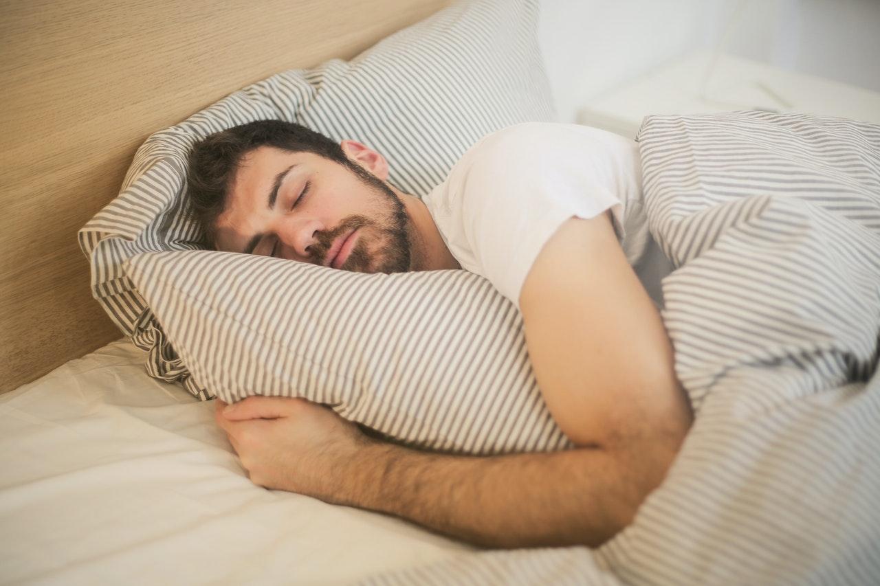 Mand ligger på siden og sover