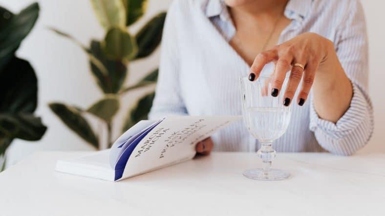 Kvinde drikker vand imens hun læser en bog