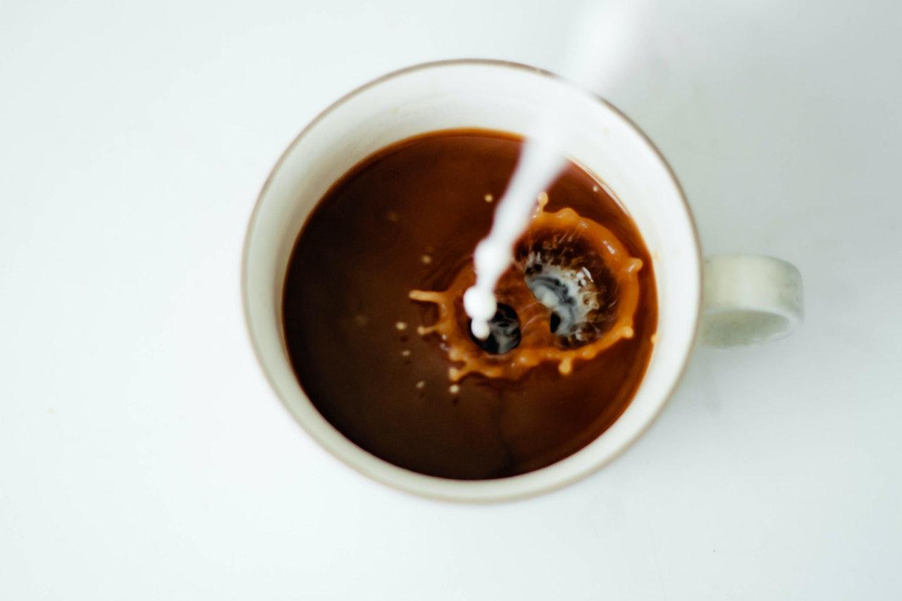 Mælk bliver hældt i kaffe