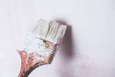 Pensel maler lyserrød farve på væg